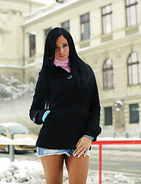 Ashley Bulgari is out in the snow wearing a short skirt and a warm top.
